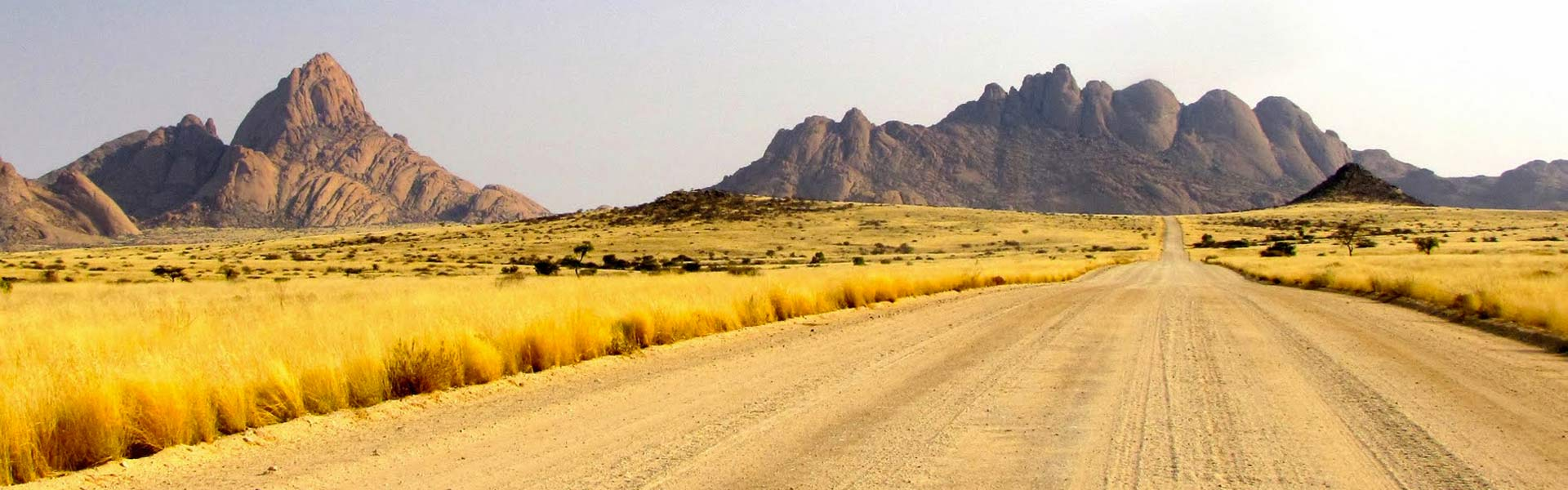 Namib desert road with the mountains of spitzkoppe ahead